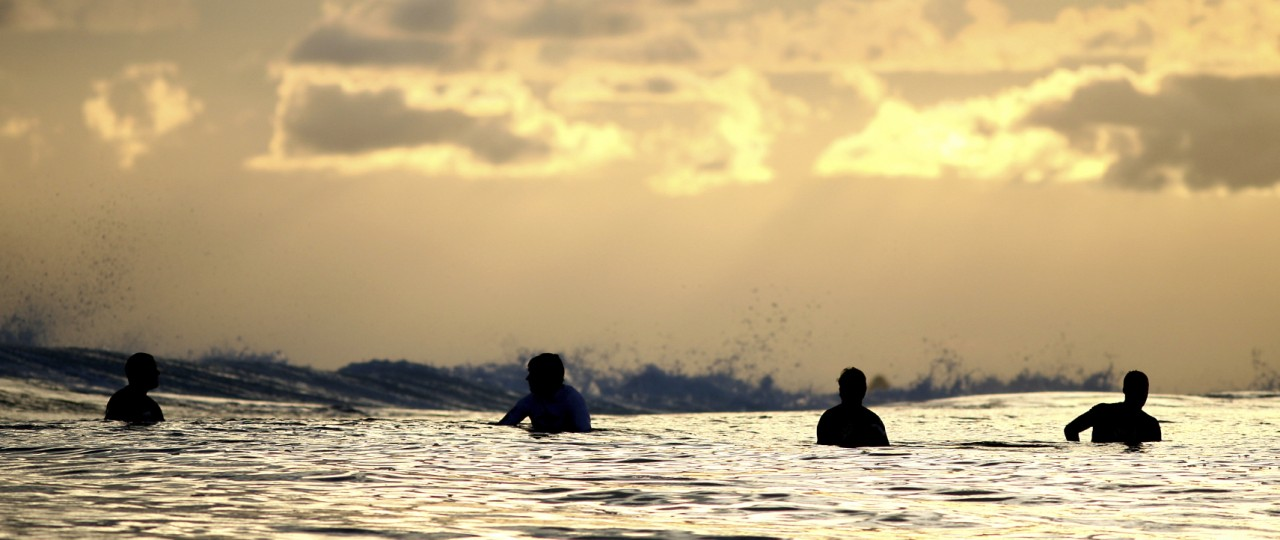 4-surfers-in-the-water-at-sunset